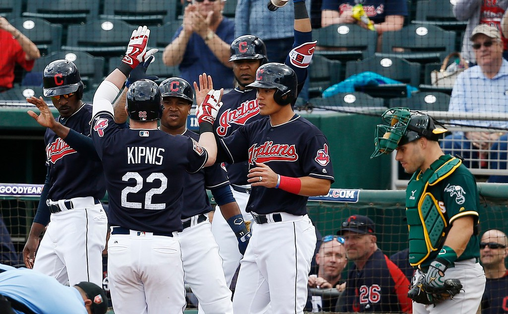 . Cleveland Indians second baseman Jason Kipnis (22) celebrates his three-run home run against the Oakland Athletics with Melvin Upton Jr, left, Jose Ramirez, third from left, Edwin Encarnacion, third from right, and Yu-Cheng Chang, second from right, as Athletics catcher Josh Phegley, right, pauses at home plate during the fifth inning of a spring training baseball game Tuesday, Feb. 27, 2018, in Goodyear, Ariz. (AP Photo/Ross D. Franklin)