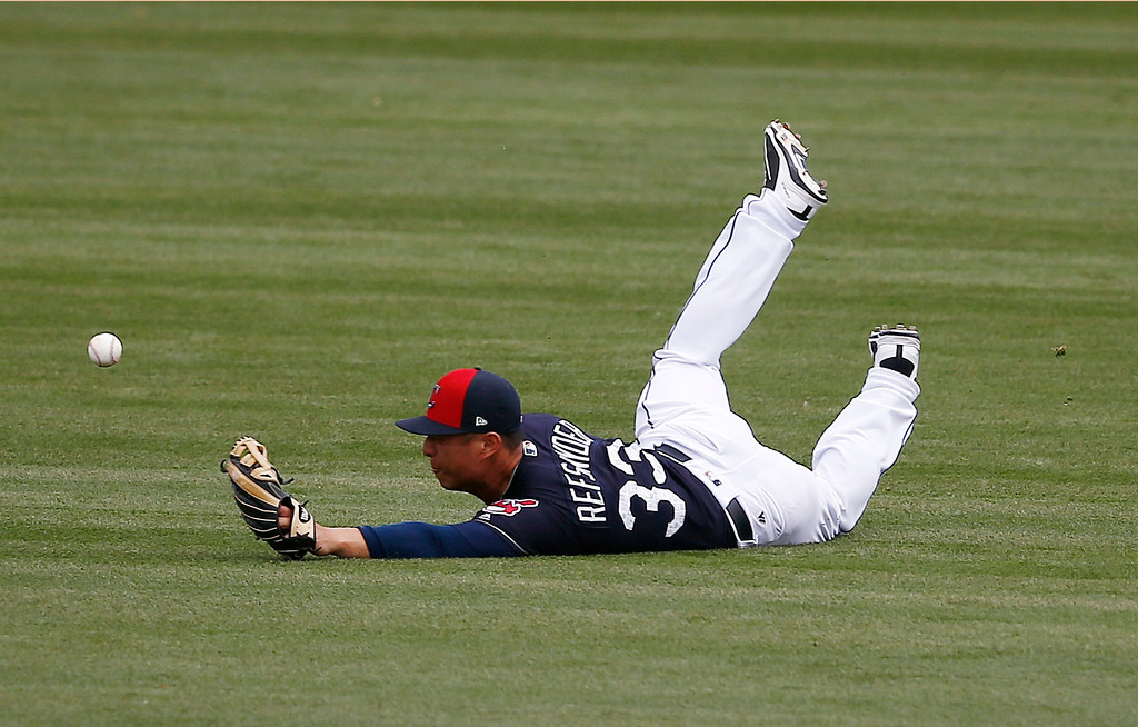 . Cleveland Indians right fielder Rob Refsnyder dives in vain for a single hit by Oakland Athletics\' Nick Noonan during the fifth inning of a spring training baseball game Tuesday, Feb. 27, 2018, in Goodyear, Ariz. (AP Photo/Ross D. Franklin)