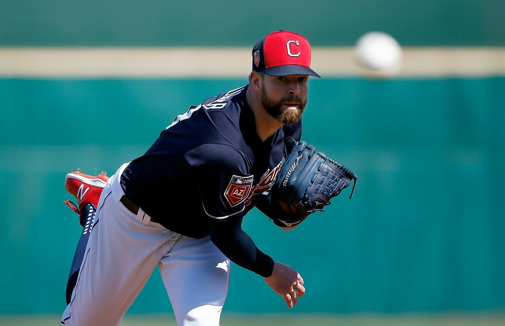 . Cleveland Indians starting pitcher Corey Kluber throws a warm up pitch before a spring training baseball game against the Oakland Athletics, Tuesday, Feb. 27, 2018, in Goodyear, Ariz. (AP Photo/Ross D. Franklin)
