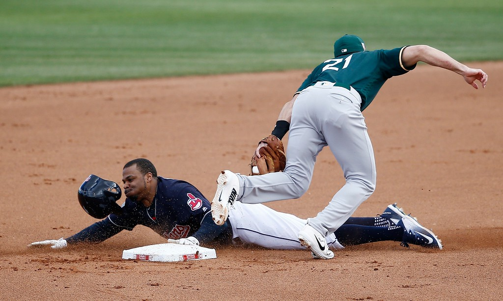 . Oakland Athletics second baseman Steve Lombardozzi (21) tags out Cleveland Indians\' Rajai Davis, left, as Davis tries to steal second base during the fourth inning of a spring training baseball game Tuesday, Feb. 27, 2018, in Goodyear, Ariz. (AP Photo/Ross D. Franklin)