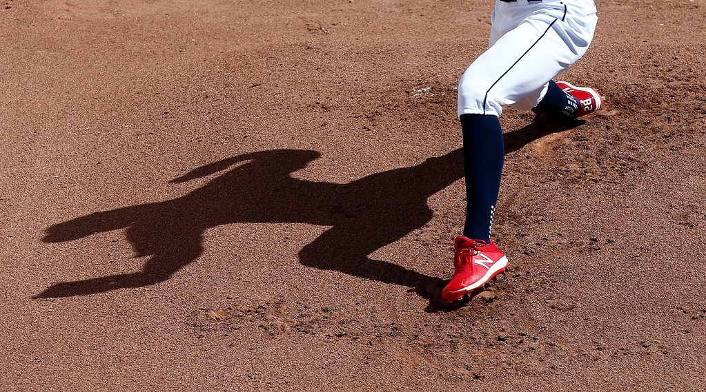 . Cleveland Indians starting pitcher Corey Kluber casts a shadow on the bullpen pitching mound dirt as he warms up before a spring training baseball game against the Oakland Athletics, Tuesday, Feb. 27, 2018, in Goodyear, Ariz. (AP Photo/Ross D. Franklin)