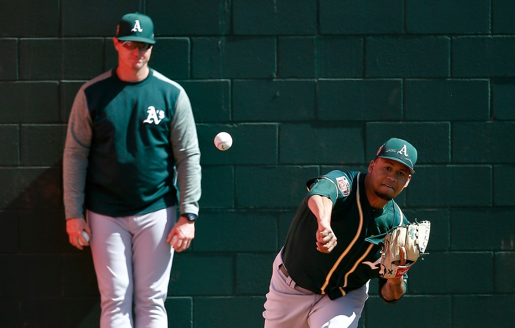 . Oakland Athletics relief pitcher Frankie Montas, right, warms up as pitching coach Scott Emerson, left, looks on prior to a spring training baseball game against the Cleveland Indians Tuesday, Feb. 27, 2018, in Goodyear, Ariz. (AP Photo/Ross D. Franklin)