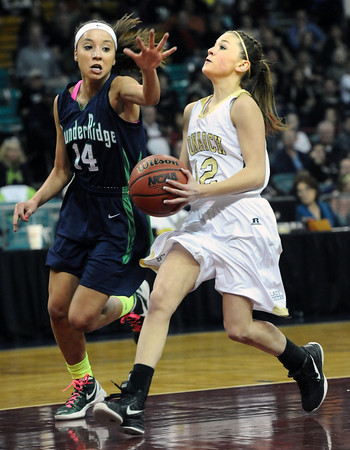 """Monarch High's Brenna Stimas (12) drives to the hoop againstThunder Ridge High's Brianna Throop (14) during their game at the Denver Coliseum on Saturday March 3, 2012.<br /> Photo by Paul Aiken / The Daily Camera /  <a href=""""http://www.bocopreps.com"""">http://www.bocopreps.com</a>"""