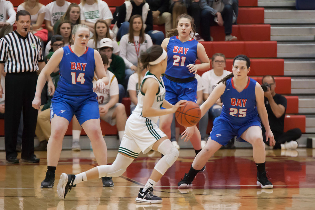 . On defense Bay girls Halle Orr (14), Haley Andrejcak (21) and Maddie Andrews (25) keep Cloverleaf\'s Cameron Tripp outside the key. Jen Forbus -- The Morning Journal