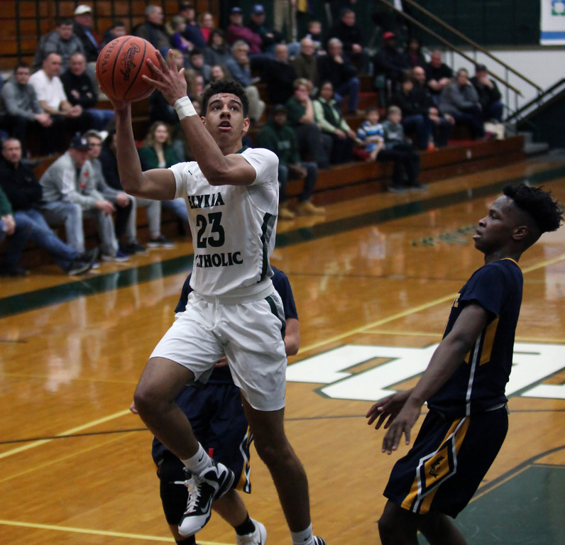 . Jarred Logan of Elyria Catholic is fouled on the shot by Neshawn Brown of Wickliffe during the second quarter. Randy Meyers -- The Morning Journal