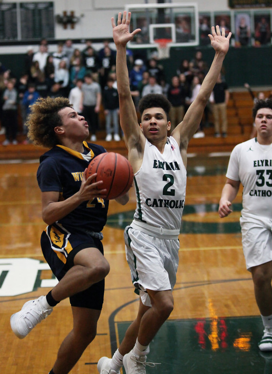 . Wickliffe\'s Anthony Olsen drives and scores past Donovan Warfield of Elyria Catholic during the third quarter. Randy Meyers -- The Morning Journal