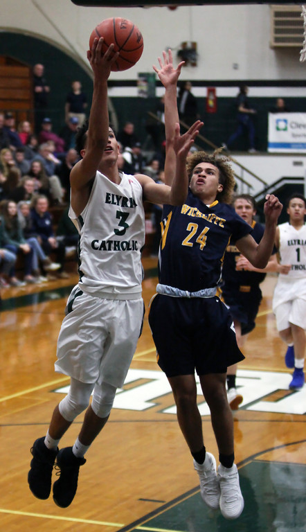 . Dorian Crutcher of Elyria Catholic drives past Anthony Olsen of Wickliffe and scores during second quarter. Randy Meyers -- The Morning Journal