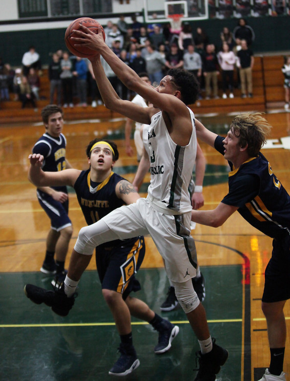 . Dorian Crutcher of Elyria Catholic drives past Dallas Zollars and Michael Galioto of Wickliffe for the score during the first quarter. Randy Meyers -- The Morning Journal