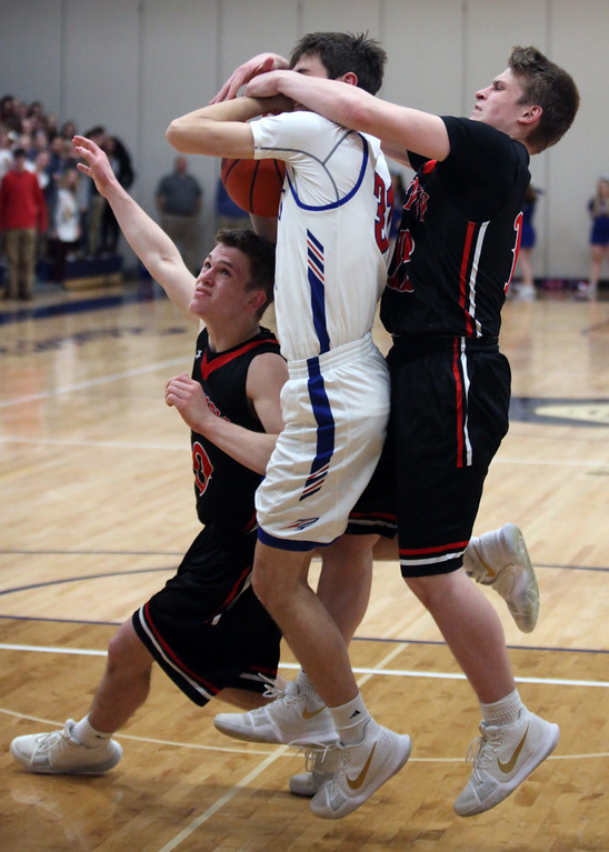 . Bay\'s Christian Dupps is caught in between Grant Howes (left) and Luke Howes of Fairview after grabbing a loose ball during the third quarter. Randy Meyers -- The Morning Journal