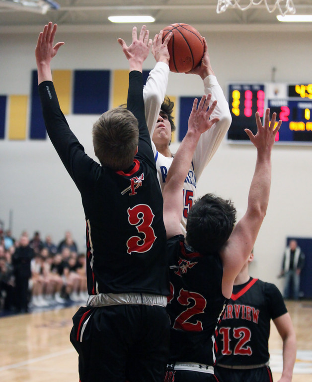 . Bay\'s R.J. Sunahara shoots and scores over Fairview\'s Colin Caja and Noah Mesaros during the first quarter. Randy Meyers -- The Morning Journal
