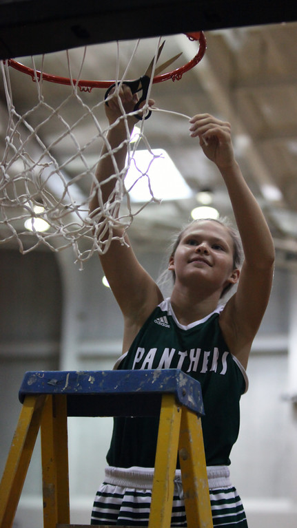 . Faith Williams cuts the net after Elyria Cathoilc defeated Chippewa at the regional finals. Randy Meyers -- The Morning Journal