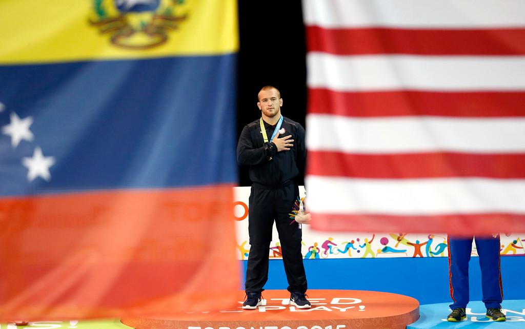 . United States\' Kyle Snyder is seen between a Venezuela flag, left, and a U.S. flag during the medal ceremony in the men\'s freestyle 97 kg wrestling competition at the Pan Am Games, Saturday, July 18, 2015, in Mississauga, Ontario. Snyder took the gold medal. (AP Photo/Julio Cortez)