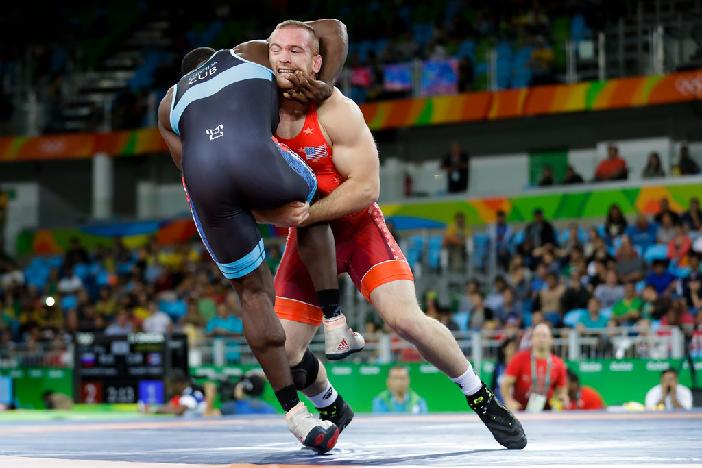 . FILE - In this Aug. 21, 2016, file photo, Kyle Snyder, of the United States, in red, competes against Cuba\'s Javier Cortina Lacerra during the men\'s 97-kg freestyle wrestling competition at the 2016 Summer Olympics in Rio de Janeiro, Brazil.It\'s been 32 years since a defending Olympic freestyle medalist returned to compete in the NCAA a year later. There will be two wrestlers to do so this year _ led by Rio gold medalist Kyle Snyder of Ohio State. (AP Photo/Markus Schreiber, File)