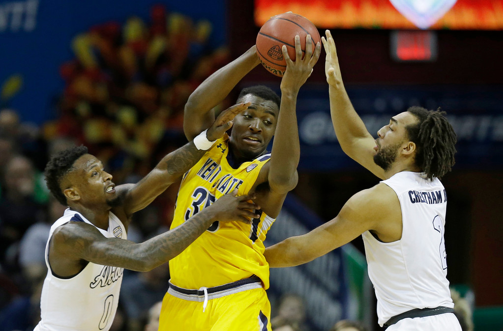 . Kent State\'s Jimmy Hall, center, looks to pass against Akron\'s Jimond Ivey, left, and Kwan Cheatham during the first half of an NCAA college basketball championship game of the Mid-American Conference tournament, Saturday, March 11, 2017, in Cleveland. (AP Photo/Tony Dejak)