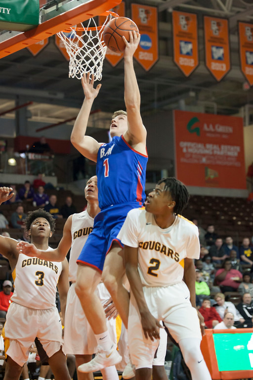 . Bay\'s Francis Sherman -- surrounded by Beechcroft Cougars -- elevates to get the basketball to the hoop. Jen Forbus -- The Morning Journal