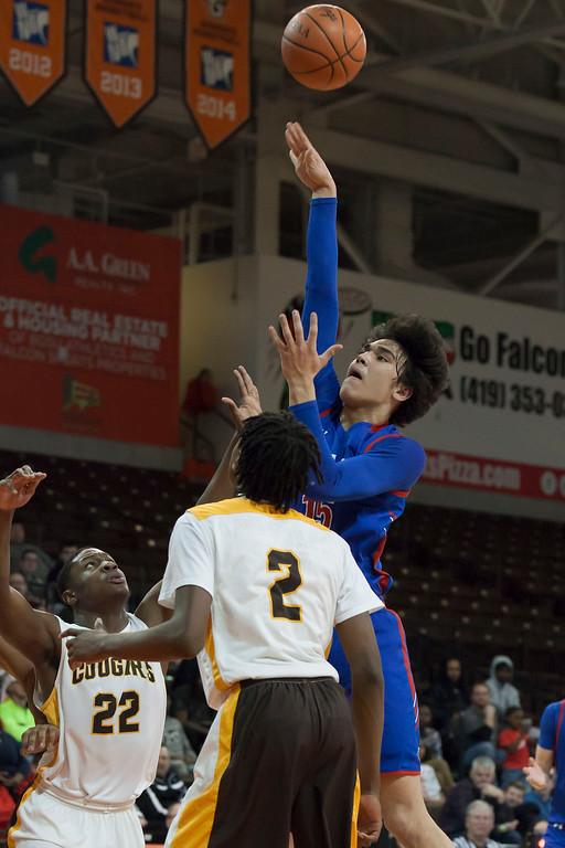. Rocket R.J. Sunahara puts the basketball up between Cougar defenders Jelani Simmons (2) and Elijah Hairston (22). jen Forbus -- The Morning Journal