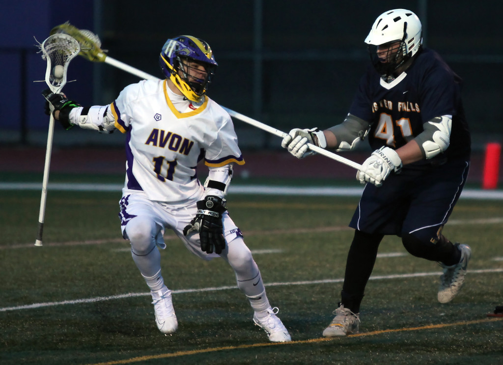 . Sam Lofton of Olmsted Falls rakes at the ball carried by Connor Walsh of Avon during the second quarter. Randy Meyers -- The Morning Journal