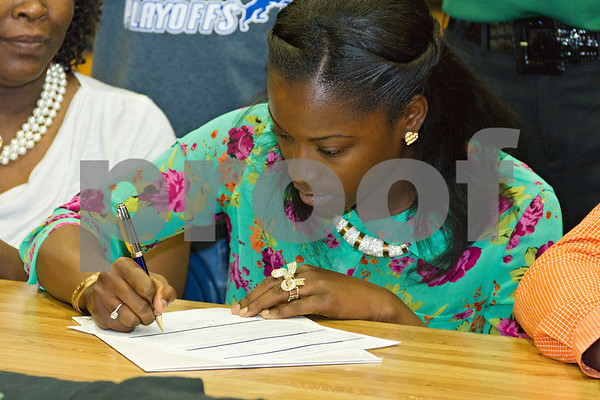 Photo by Shannon Wilson / Tyler Morning Telegraph Tiaka Lee, a senior at John Tyler High School, signs a letter of intent to play basketball with Panola College while family, friends and coaches look on.