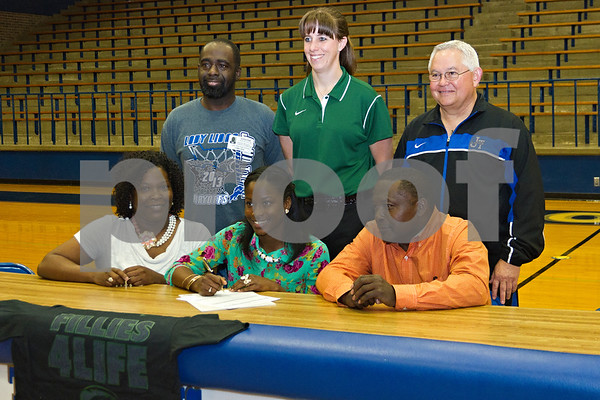 Photo by Shannon Wilson / Tyler Morning Telegraph Tiaka Lee, a senior at John Tyler High School, signs a letter of intent to play basketball with Panola College while family, friends and coaches look on.  (Bottom Row) Myesha Lee, Tiaka Lee's mother, Tiaka Lee, Eddie Lee, grandfather, (Top Row) Orlando Wickware, family friend, Coach of Panola College Women's Basketball Tracey Stellato and John Tyler Coach Mike Smith (top row).