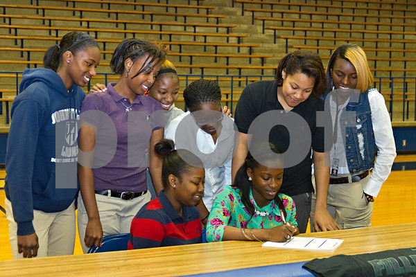 Photo by Shannon Wilson / Tyler Morning Telegraph Tiaka Lee, a senior at John Tyler High School, signs a letter of intent to play basketball with Panola College while teammates look on in the John Tyler varsity gym on Monday morning.