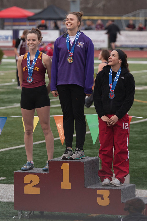 . Kamryn Sharer of Avon makes two visits to the top spot on the winner\'s podium Friday at the Lorain County Invitational. Here she receives her medal for a first place win in the girl\'s long jump event. Jen Forbus -- The Morning Journal