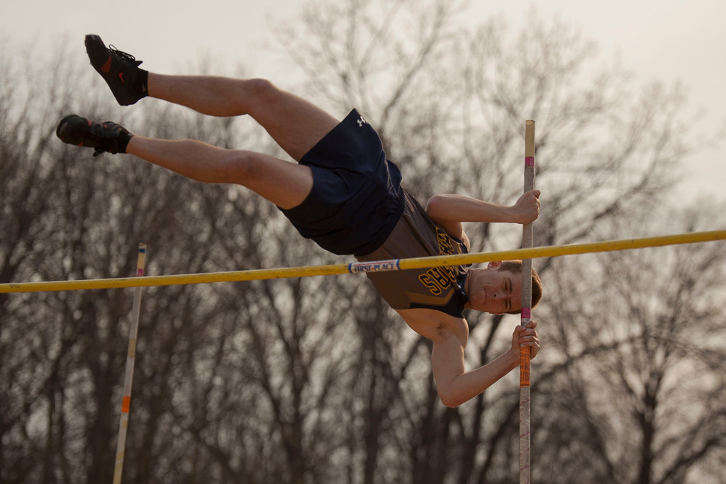 . North Ridgeville\'s Matthew Caraszi hoists himself over the crossbar in the boys pole vault event of the Lorain County Invitational Track Meet. Jen Forbus -- The Morning Journal