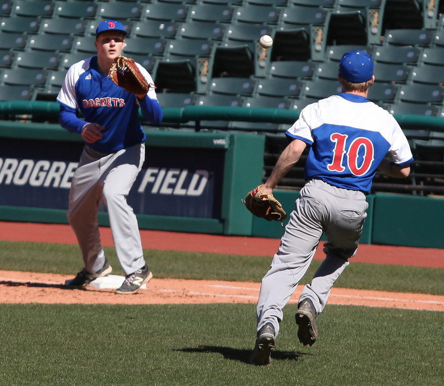 . Bay pitcher Dillon Barry flips the ball to first baseman Thomas Koss for the out against Eastlake North. Randy Meyers -- The Morning Journal