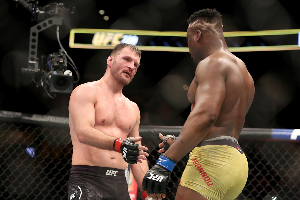 . Stipe Miocic, left, shakes hands with Francis Ngannou after their heavyweight championship mixed martial arts bout at UFC 220, early Sunday, Jan. 21, 2018, in Boston. Miocic retained his title via unanimous decision. (AP Photo/Gregory Payan)
