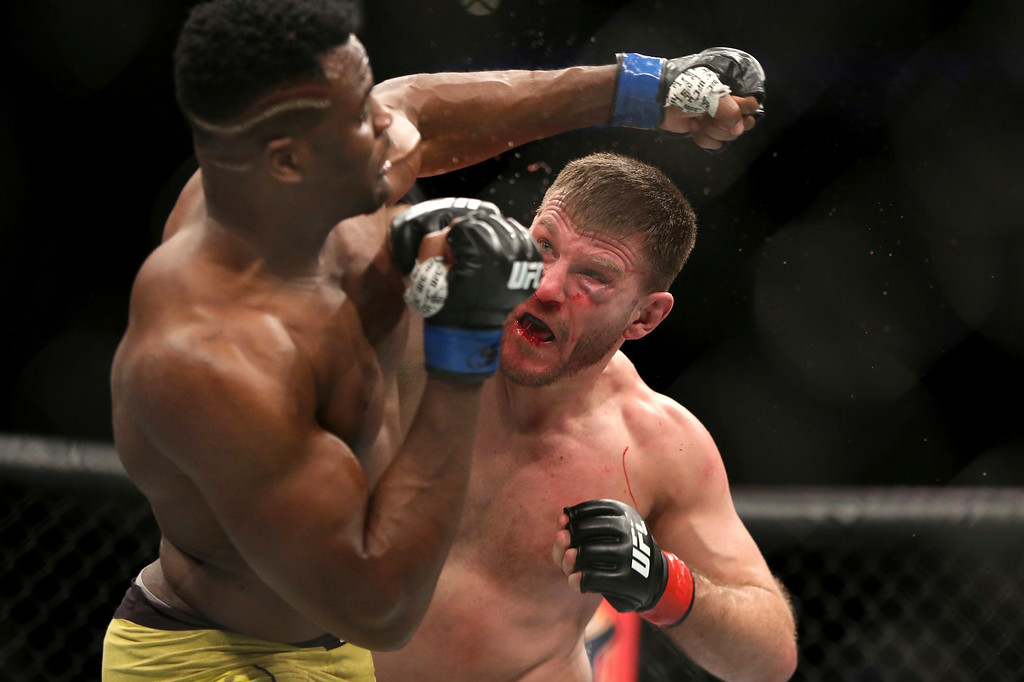 . Stipe Miocic, right, lands a right hand against Francis Ngannou during a heavyweight championship mixed martial arts bout at UFC 220, early Sunday, Jan. 21, 2018, in Boston. Miocic retained his title via unanimous decision. (AP Photo/Gregory Payan)