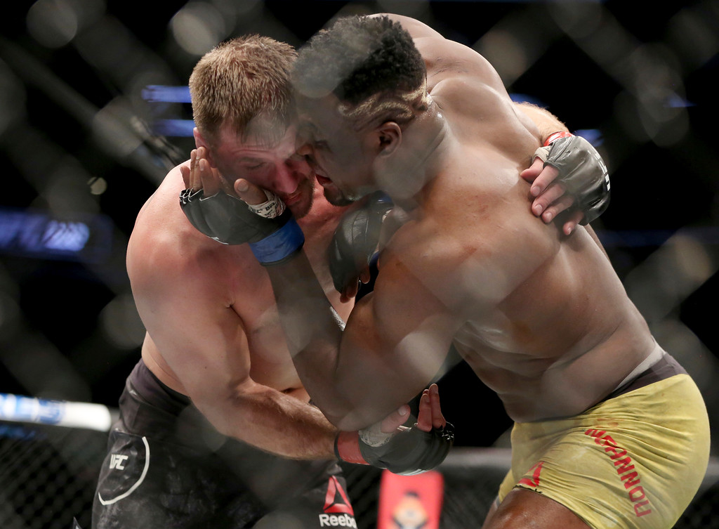 . Stipe Miocic, left, engages with Francis Ngannou during a heavyweight championship mixed martial arts bout at UFC 220, early Sunday, Jan. 21, 2018, in Boston. Miocic retained his title via unanimous decision. (AP Photo/Gregory Payan)