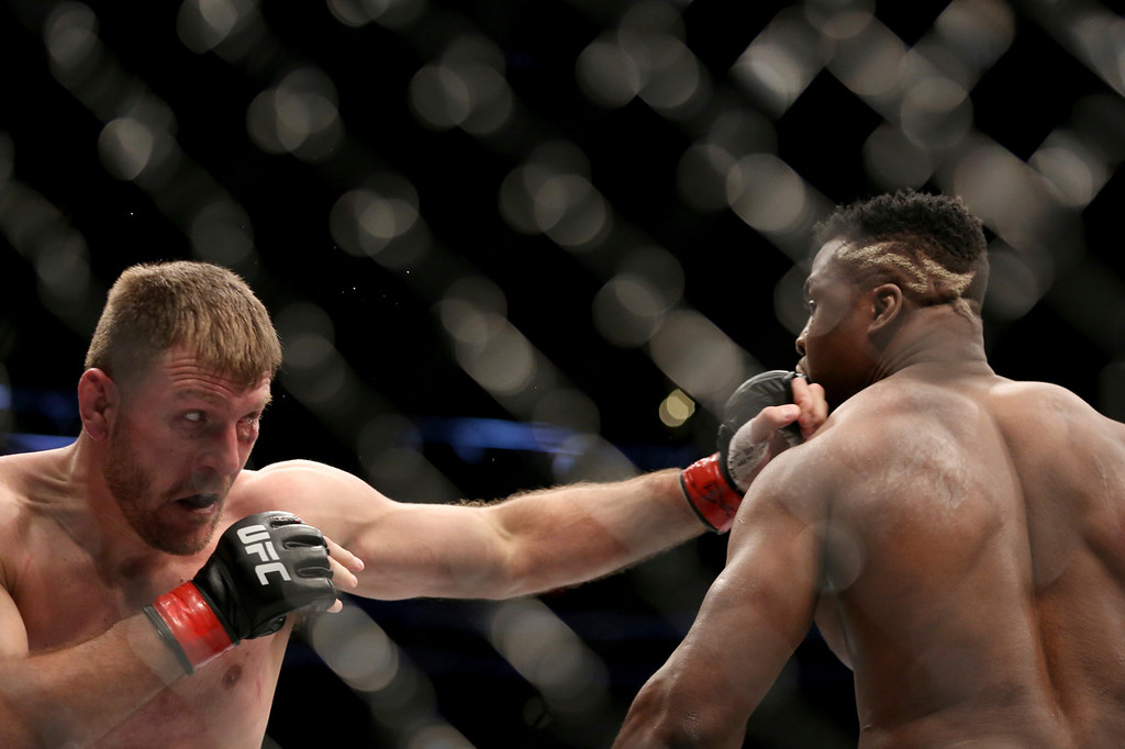 . Stipe Miocic, left, lands a jab against Francis Ngannou during a heavyweight championship mixed martial arts bout at UFC 220, Sunday, Jan. 21, 2018, in Boston. Miocic retained his title via unanimous decision. (AP Photo/Gregory Payan)