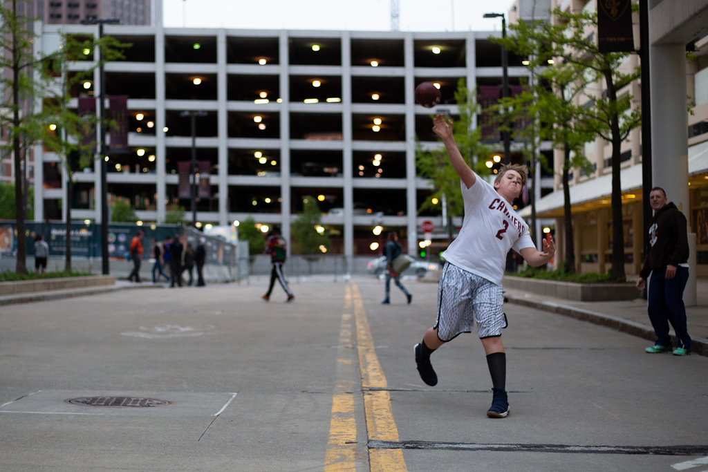 . Michael Johnson - The News-Herald Braylon Woods throws a football to his siblings outside of the Quicken Loans Arena during the Eastern Conference Finals game 2 watch party on May 15, 2018.