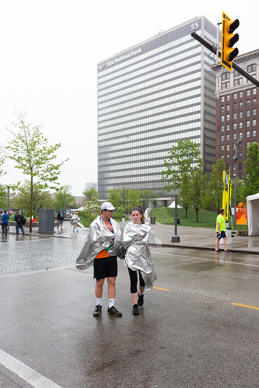 . Michael Johnson - The News-Herald Cleveland Marathon participants try to get warm after running on Sunday morning.