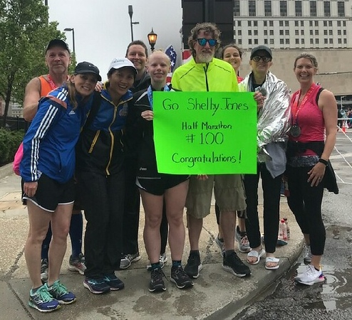 . Courtesy Shelby Jones Mentor resident Shelby Jones, left and holding sign, celebrates with friends after completing her 100th half-marathon on May 20.
