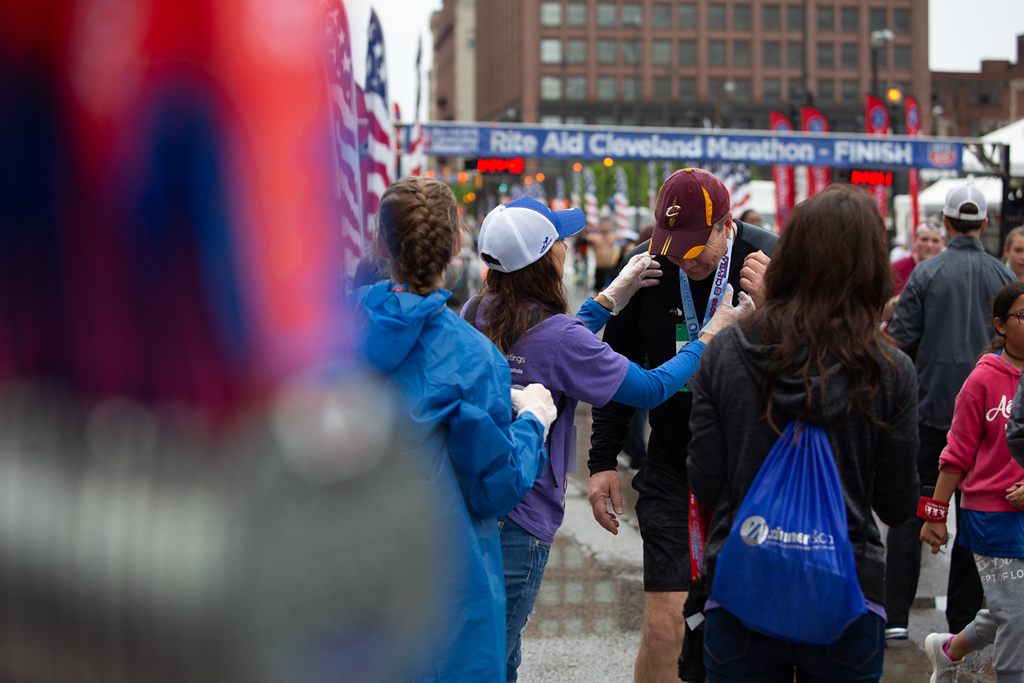 . Michael Johnson - The News-Herald Volunteers hand out medals at the Cleveland Marathon on May 20, 2018.