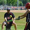 Paul DiCicco - The News-Herald<br /> Mentor Big Red coach Michael Rowan of Mentor, pitches soft-toss to Jude Iliano also of Mentor, at the Willoughby Starzz Invitational softball tournament on June 10.