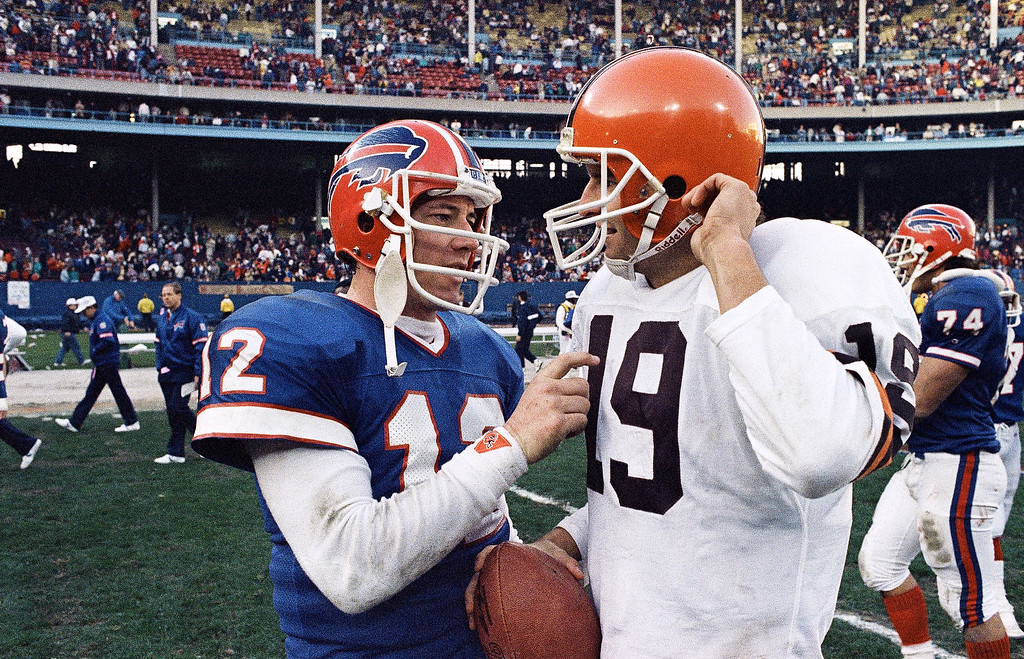 . Buffalo Bills quarterback Jim Kelly (12) playfully pokes Cleveland Browns quarterbacks Bernie Kosar in the chest following the Browns 27-21 win over Kelly and the Bills Sunday in Cleveland, Ohio, Nov. 15, 1987. Kelly and Kosar were college teammates at the University of Miami. (AP Photo/Mark Duncan)