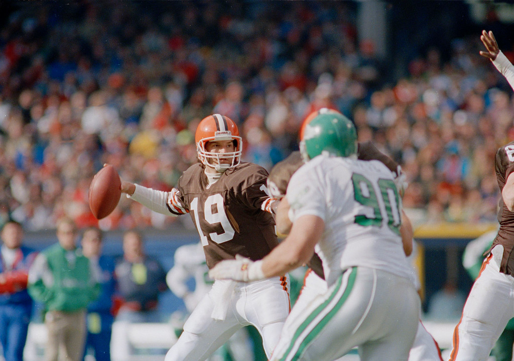 . Cleveland Brown\'s quarterback Bernie Kosar (19) winds up to throw in the first quarter as Philadelphia Eagles defensive tackle Mike Golic (90) rushes in Cleveland, Nov. 10, 1991. (AP Photo/Jeff Haynes)