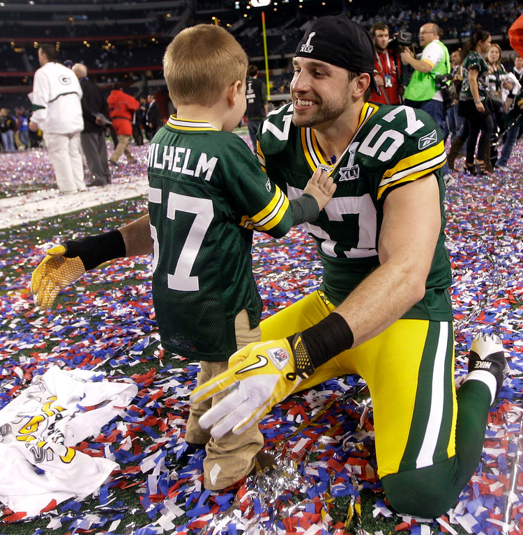 . Green Bay Packers\' Matt Wilhelm celebrates with his son Mason after beating the Pittsburgh Steelers 31-25 in the NFL football Super Bowl XLV game Sunday, Feb. 6, 2011, in Arlington, Texas. (AP Photo/David J. Phillip)