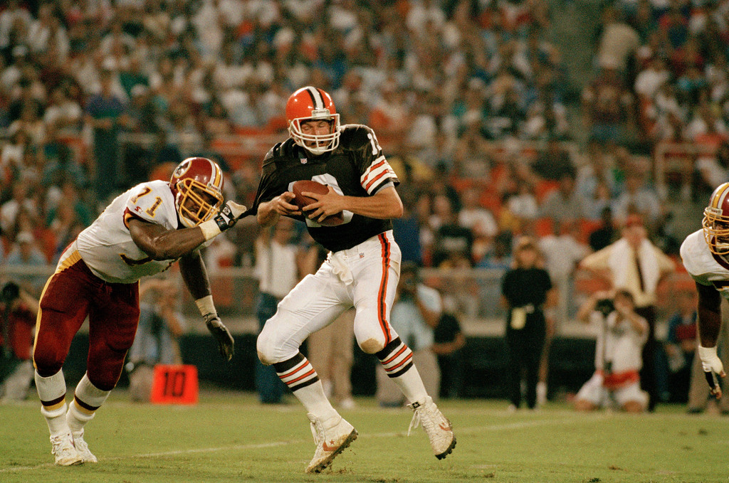 . Washington Redskins defensive end Charles Mann (71) grabs hold of Cleveland Browns quarterback Bernie kosar (12) for a sack during the second quarter at Washington\'s RFK Stadium, Aug. 9, 1993. The Browns lost 12 yards on the play. The Redskins defeated the Browns 41-12. (AP Photo/Doug Mills)