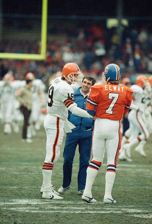 . Cleveland Browns quarterback Bernie Kosar shakes hands with Denver Broncos quarterback John Elway during warm-ups before their AFC Championship game on Sunday, Jan. 11, 1987 in Cleveland. (AP Photo/Rob Kozloff)