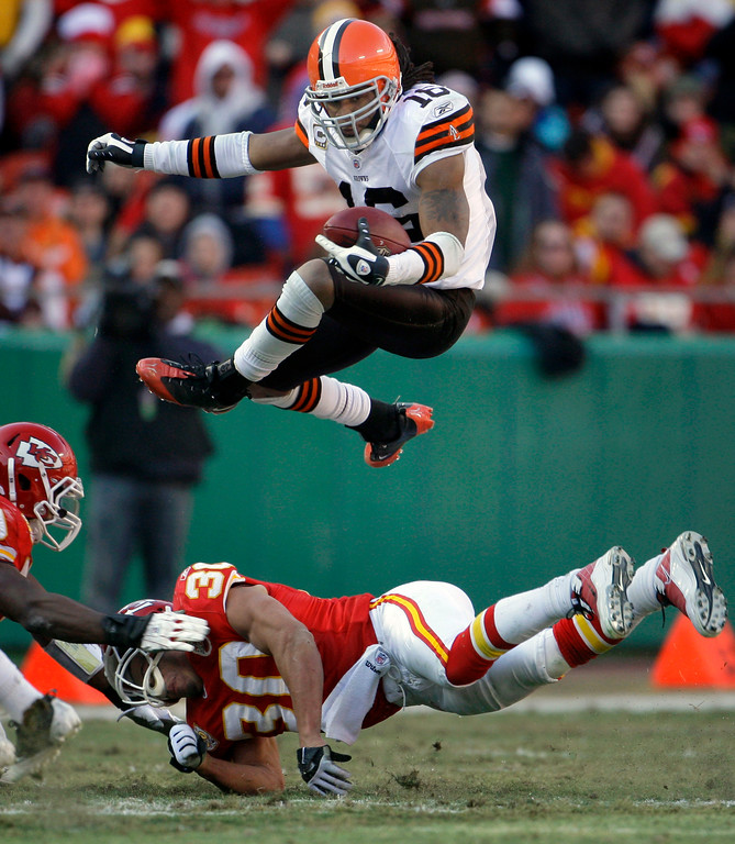 . Cleveland Browns wide receiver Josh Cribbs (16) leaps over Kansas City Chiefs safety Mike Brown (30) while running for a short gain during the third quarter of an NFL football game Sunday, Dec. 20, 2009, in Kansas City, Mo. The Browns won 41-34. (AP Photo/Charlie Riedel)