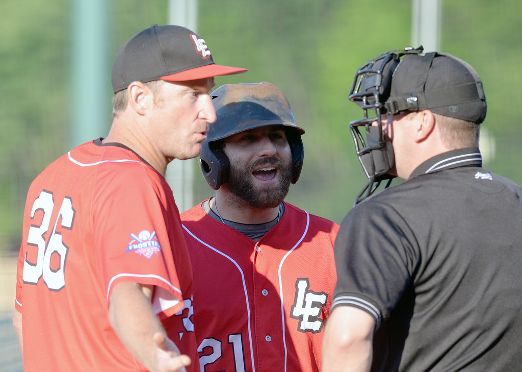 . Morning Journal File Crushers manager Chris Mongiardo, left, and designated hitter Andrew Davis, center, have a discussion with home plate umpire Kyle Rees after Rees threw Davis out of the game in the top of the first inning for arguing balls and strikes in a game against Rockford at All Pro Freight Stadium on June 26.