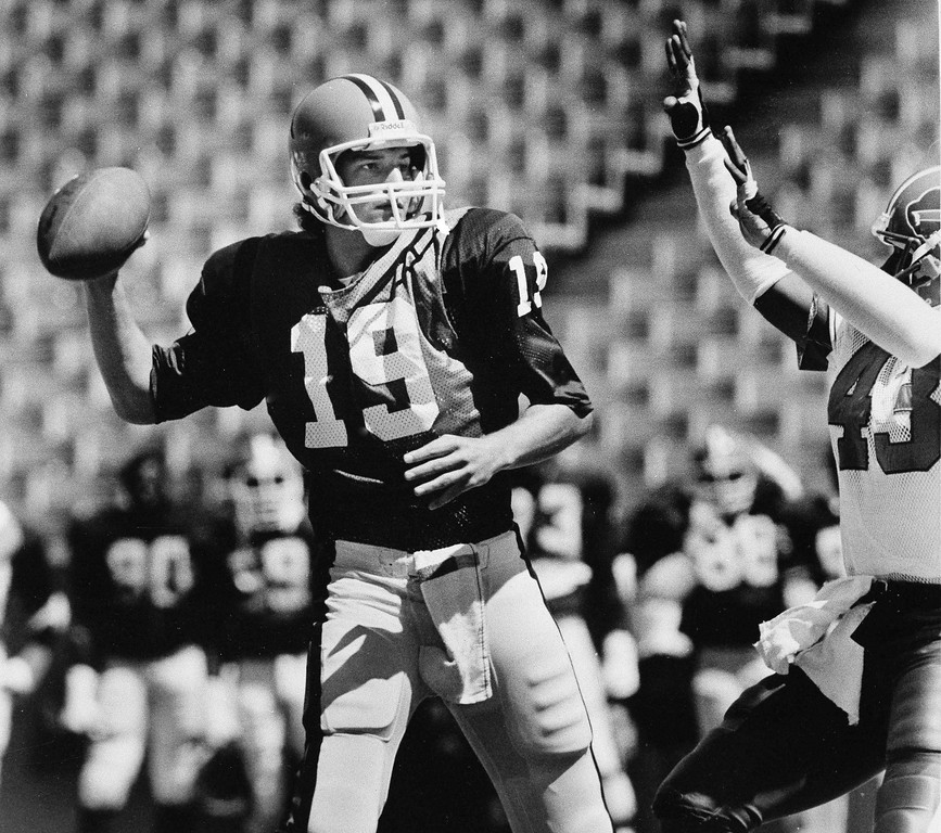 . Bernie Kosar, the Cleveland Brown rookie quarterback acquired in the NFL\'s supplemental draft this year, gets pressure from Buffalo Bill safety Martin Bayless (43) as he prepares to release the ball during scrimmage at Rich Stadium, Orchard Park, N.Y., Aug. 5, 1985. (AP Photo/Rob McElroy)