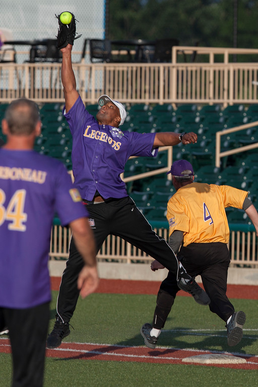 . Jen Forbus - The Morning Journal<br> Je\'Rod Cherry jumps to catch the throw to first, allowing former sports broadcaster Ron Jantz to make it to the bag during the Cleveland Legends softball game on June 23 at Sprenger Stadium.