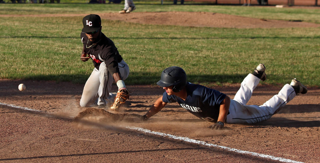 . Randy Meyers - The Morning Journal Ironmen first baseman Robert Williams loses the ball on the throwdown from the catcher as Joe Raffin of the Spartans dives back safely on Monday.