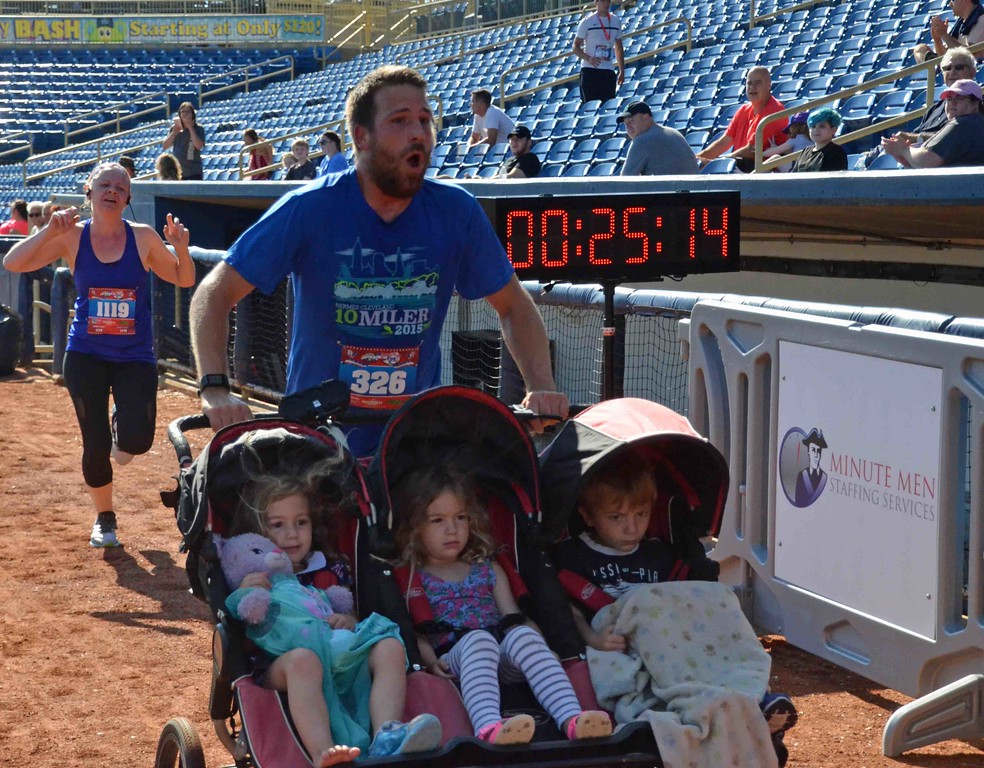 . Paul DiCicco - The News-Herald Father of at least three, Chris Toth (38), finishing the race pushing the family.