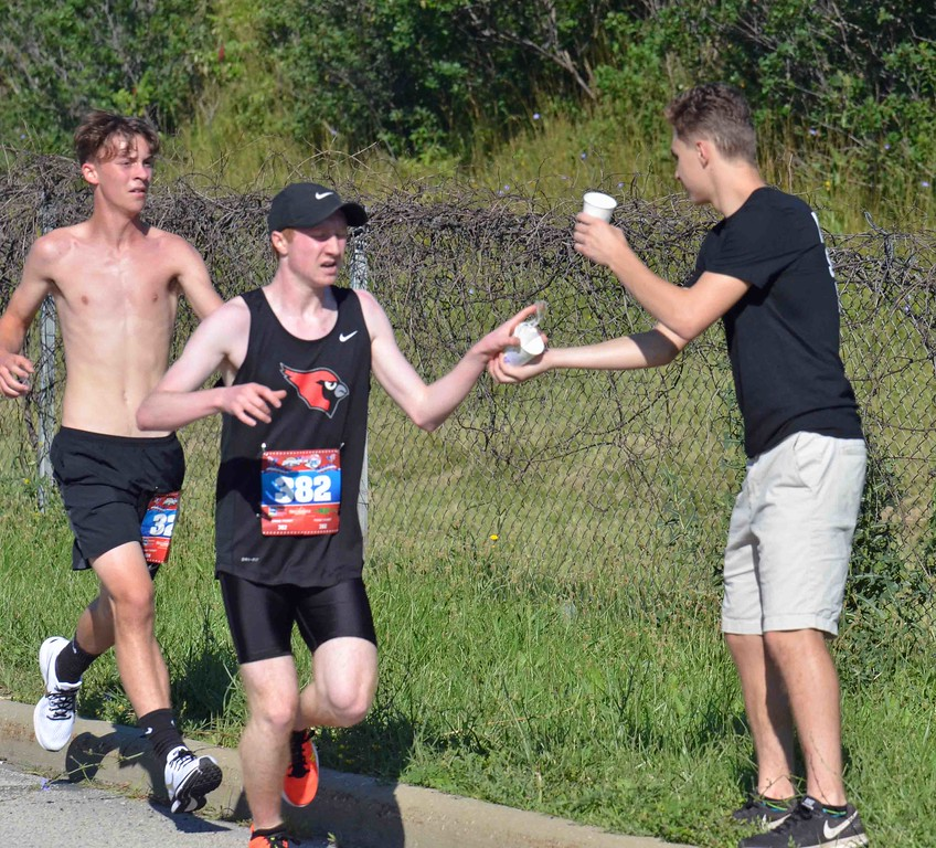 . Paul DiCicco - The News-Herald Mentor\'s Nick Kozlowski getting a water as he nears the half-way mark of the 2017 Captains Grand Slam 5K on July 2.