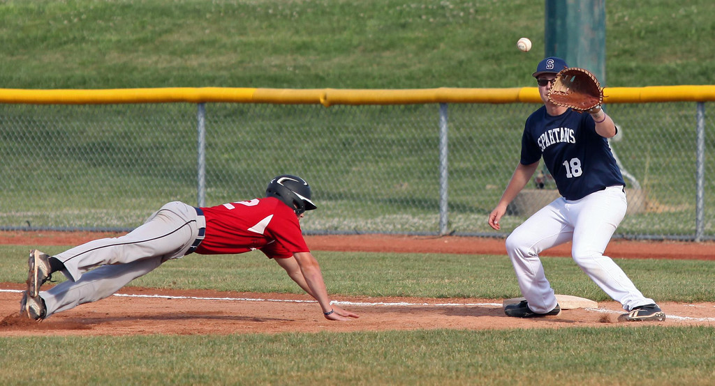 . Randy Meyers - The Morning Journal Jesse Barrios of the Ironmen dives back to first safely as Nathan Hendrix of the Spartans waits on the throw during Monday\'s game at the Pipeyard