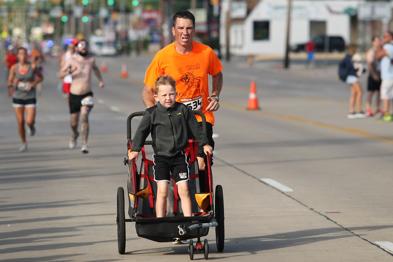 Michael Johnson - The News-Herald<br />  Bryan Nelson runs along side his son during the final stretch of the 40th Johnnycake Jog on July 10, 2016.